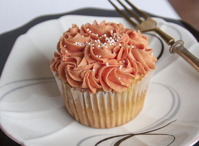 Cupcakes piped with coral-colored Creamed Frosting and sprinkled with INDIA TREE String of Pearls Party Decoratifs make the perfect Autumn dinner party dessert.