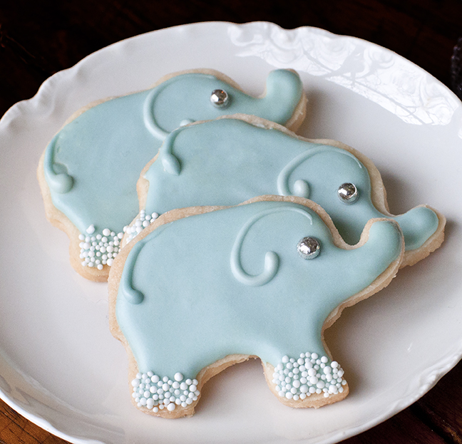 These Elephant Shortbread Cookies are sure to delight the child in everyone, yet are sophisticated enough to be served at a shower, a reception, or a tea.  A simple recipe that creates melt-in-your-mouth results, Shortbread Cutout Cookies made with INDIA TREE Fondant and Icing Sugar keep their shape as they bake.  These are decorated with Royal Icing, tinted with INDIA TREE Nature's Colors Decorating Colors, INDIA TREE Nature's Colors String of Pearls and INDIA TREE Silver Dragées.