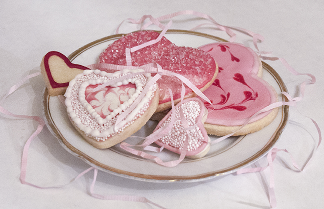 Flood heart-shaped Shortbread Cookies with Royal Icing tinted with INDIA TREE Nature's Colors Red Decorating Color. Add drops gradually to get a beautiful range of pinks. Top with INDIA TREE Nature's Colors Decorating Sugars and String of Pearls Decoratifs.