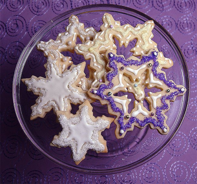 Gorgeous Snowflake Cookies made with our Sugar Cookies Recipe for larger cookies. The dough is firmer, preventing the cookie from spreading in the pan during baking or breaking into pieces during decorating. The perfect choice for these intricately shaped snowflakes flooded and piped with Royal Icing and flocked with either INDIA TREE Sparkling Sugars or INDIA TREE Nature's Colors Decorating Sugar. INDIA TREE French Dragées add the finishing touch.